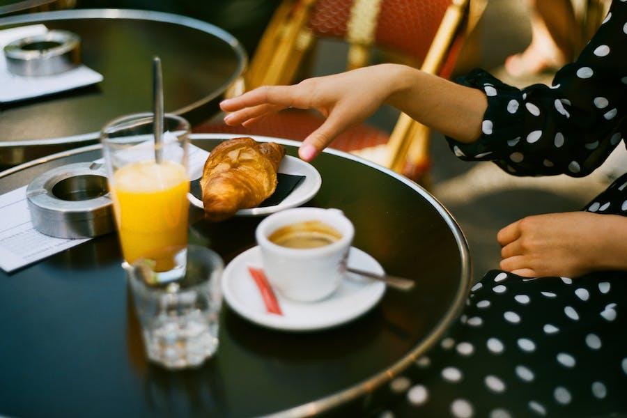 un petit déjeuner : jus d'orange, café et croissant