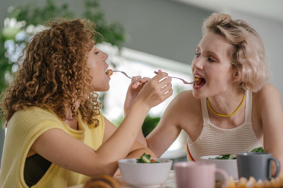 deux femmes partageant des aliments avant de les mâcher