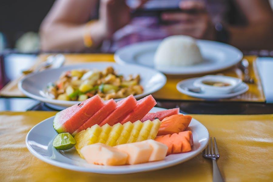 Un assiette des fruits riches en l'eau suivi d'un assiettes de légumes cuits