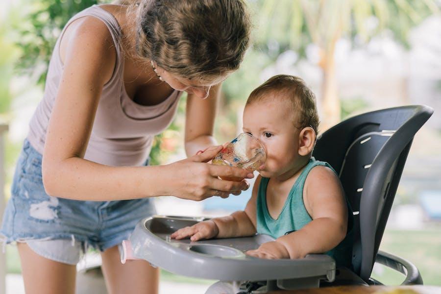 Femme en donnant de l'eau à son enfant