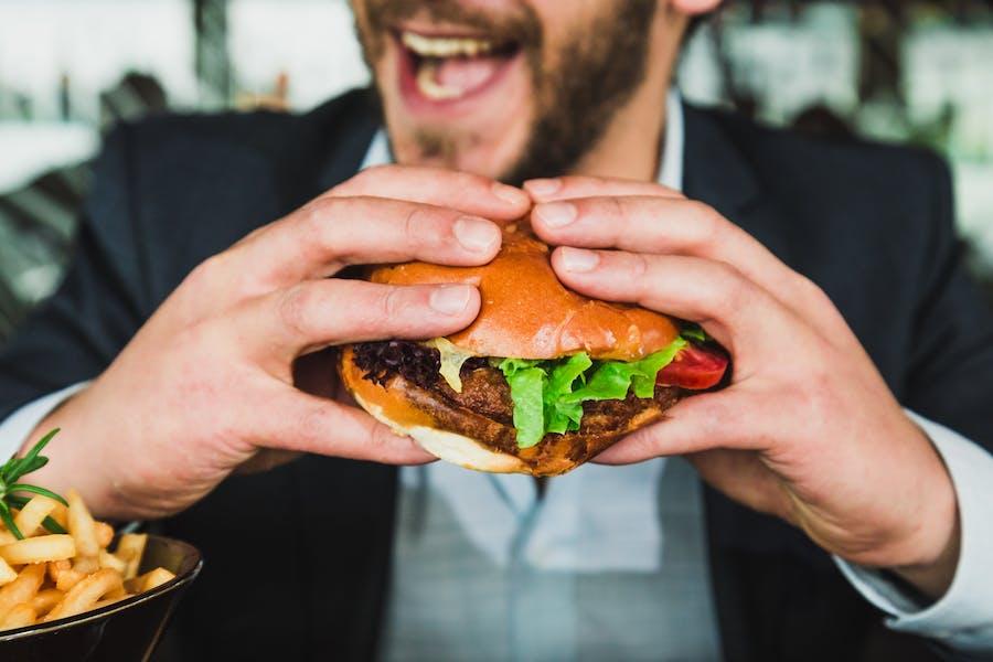 homme mangeant un hamburger