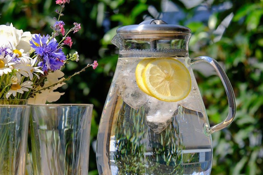 Pichet à l'eau avec des glaçons et des rondelles de citron jeune